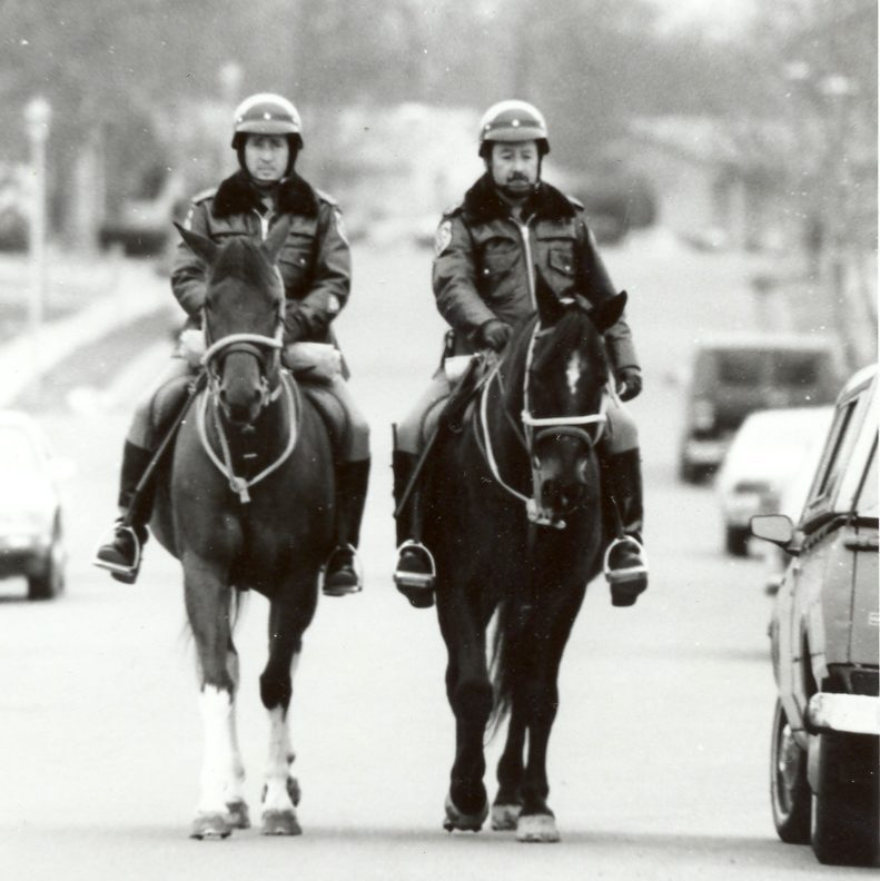 Two mounted patrol officers patrol a road with leather jackets on.